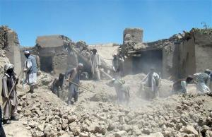 Afghan men search for the bodies of people killed in a NATO airstrike in Logar province
