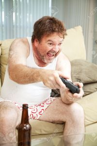 Middle aged man in his underwear playing video games and drinking beer.